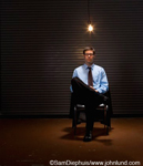 Businessman sitting under light bulb